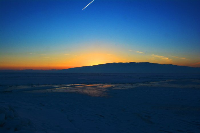 A last sunset shot taken on top of a pile of ice chunks. Note the con trail.